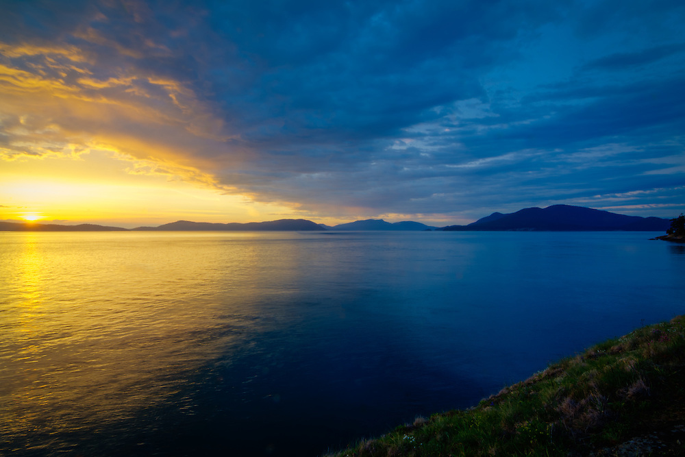 An insanely vibrant and colorful sky over Rosario Strait as the sun sets behind Washington's  Decateur and Lopez Islands in the Strait of Juan de Fuca. This view shows Blakely Island to the left and Cypress Island to the right. Photographed from Fidalgo Island in Anacortes.