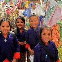 Asia, Bhutan, Paro. Young Bhutanese school girls cross bridge of prayer flags.