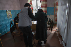 Dr Moshin Mehraj assists an elderly patient at the MSF mobile clinic in the village of Gorodishe, near Lugansk.