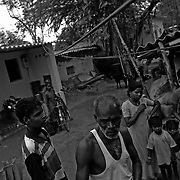 Residents of a small village are seen outside their dwellings made with broken asbestos roof tiles in a small slum located on the outskirts of Ahmedabad, India. The entire community is built on top of and from the asbestos scraps and dumps from decades of production at the Shree Digvijay Cement Plant.  Almost every single residence in this and many villages and cities like this in India have asbestos cement products in them. Broken sheets of asbestos cement products can release deadly fibres into the air.