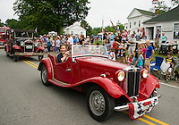 Barbara and Addison Philpot drive the parade route in style with Harris Philpot behind the wheel of his MG during the Gilmanton 4th of July parade on Saturday morning.  (Karen Bobotas/for the Laconia Daily Sun)