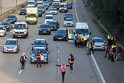 Ockham, UK. 21st September, 2021. Insulate Britain climate activists begin to block the anticlockwise carriageway of the M25 between Junctions 9 and 10 as part of a campaign intended to push the UK government to make significant legislative change to start lowering emissions. Both carriageways were briefly blocked before being cleared by Surrey Police. The activists are demanding that the government immediately promises both to fully fund and ensure the insulation of all social housing in Britain by 2025 and to produce within four months a legally binding national plan to fully fund and ensure the full low-energy and low-carbon whole-house retrofit, with no externalised costs, of all homes in Britain by 2030.