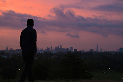 Primrose Hill, London, September 22nd 2016. A man admires the city skyline on Primrose Hill as the autumn equinox sun rises over London . ©Paul Davey<br /> FOR LICENCING CONTACT: Paul Davey +44 (0) 7966 016 296 paul@pauldaveycreative.co.uk