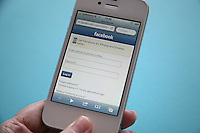 White iPhone 4s with Facebook login page on Safari browser