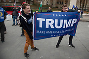 Pro Trump protester waving a Trump - Make America Great Again flag in Westminster opposite Parliament on the as five days of Brexit debate begins on 4th December 2018 in London, England, United Kingdom.