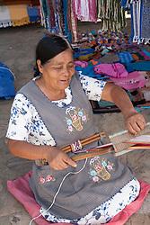 North America, Mexico, Oaxaca Province, Oaxaca, woman using backstrap loop to weave belt