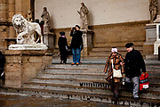 Tourists visiting Romano Greek statues in the Piazza della Sinoria, Florence.<br /> Piazza della Signoria is an L-shaped square in front of the Palazzo Vecchio in Florence, Italy. It was named after the Palazzo della Signoria, also called Palazzo Vecchio.<br /> It is the focal point of the origin and of the history of the Florentine Republic and still maintains its reputation as the political hub of the city.It is the meeting place of Florentines as well as the numerous tourists, located near Ponte Vecchio and Piazza del Duomo and gateway to Uffizi Gallery.<br /> The Loggia dei Lanzi consists of wide arches open to the street, three bays wide and one bay deep. The arches rest on clustered pilasters with Corinthian capitals. The wide arches appealed so much to the Florentines, that Michelangelo even proposed that they should be continued all around the Piazza della Signoria<br /> It is effectively an open-air sculpture gallery of antique and Renaissance art including the Medici lions.