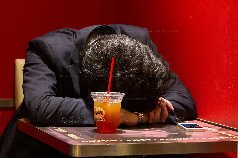A Japanese salaryman sleeping at a table in a Segafredo cafe in Nakameguro Tokyo, Japan. Friday June 8th 2018