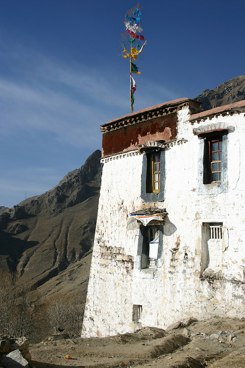 this is a common site in tibet, prayer flags adorning everything, this is on the roof staff of a monastery in tibet