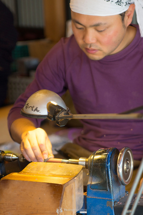 A young man making pens on a lathe for tourists.