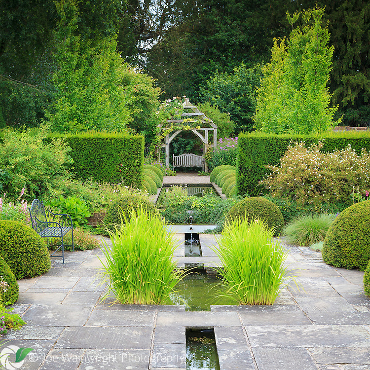 Two rills, one wide and the other narrow, make up this section of Wollerton Old Hall Gardens, Shropshire.  Other features include York stone paving and Buxus sempervirens balls. This image is available for sale for editorial purposes, please contact me for more information.