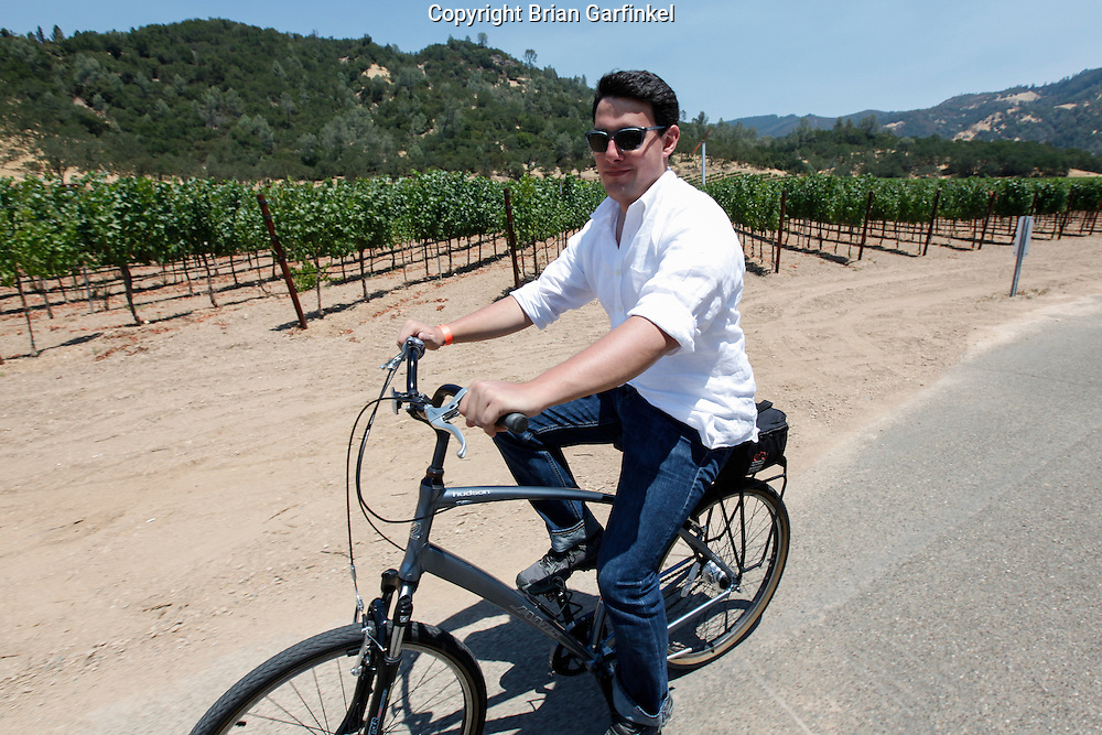 Christopher rides past a vineyard on Sunday July 15th 2012 in Calistoga, California. (Photo By Brian Garfinkel)