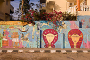 Flowering Bougainvillea and the matching colours of modern hieroglyphic artwork painted on a house's wall on local wasteground in the village of Gezirat, West Bank of Luxor, Nile Valley, Egypt.