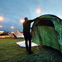 Nederland, Amsterdam , 1 oktober 2014.<br /> De rij caravans met mensen die een zelfbouwkavel willen kopen op het Zeeburgereiland wordt steeds groter.<br /> Sommige staan al een paar weken in de wachtrij totdat ze een kavel mogen kopen. Pas volgende week zaterdag gaan de kavels pas in de verkoop, maar wie weg gaat, verliest zijn plek in de rij.<br /> Een van de kampeerders staat er al een tijdje in zijn caravan: 'Ik ben hier behoorlijk vroeg gaan staan, want er is één kavel waar ik echt geïntresseerd in ben. Er hoeft er maar een eerder te zijn en dan ben je 'm kwijt.'<br /> De wachtende kopers vinden het best gezellig op het terrein: 'Je ontmoet een soort van je toekomstige buren als het zo doorgaat. Dat geeft een apart campinggevoel en we barbecuen samen.'<br /> Een probleempje, als je weggaat ben je je plek kwijt. 'Als je moet werken moet je zorgen dat er iemand anders op je plek zit. Ik had hier eerst helemaal geen zin in, maar het is toch wel een bizar avontuur.'<br /> Op de foto: Een nieuwkomer slaat zijn tent op.<br /> Foto:Jean-Pierre Jans