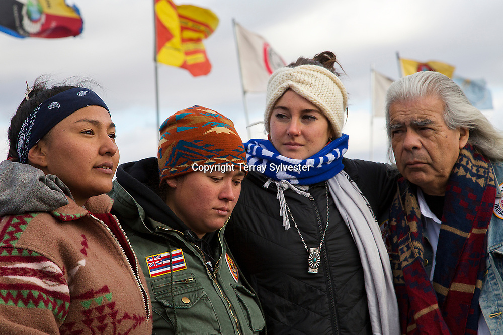 From left, activists Lauren Howland and Malia Hulleman, actress Shailene Woodley, and Gray Wolf, director of the Southern California Chapter of the American Indian Movement, embrace in the opposition camp against the Dakota Access oil pipeline on November 18, 2016. Cannon Ball, North Dakota, United States.
