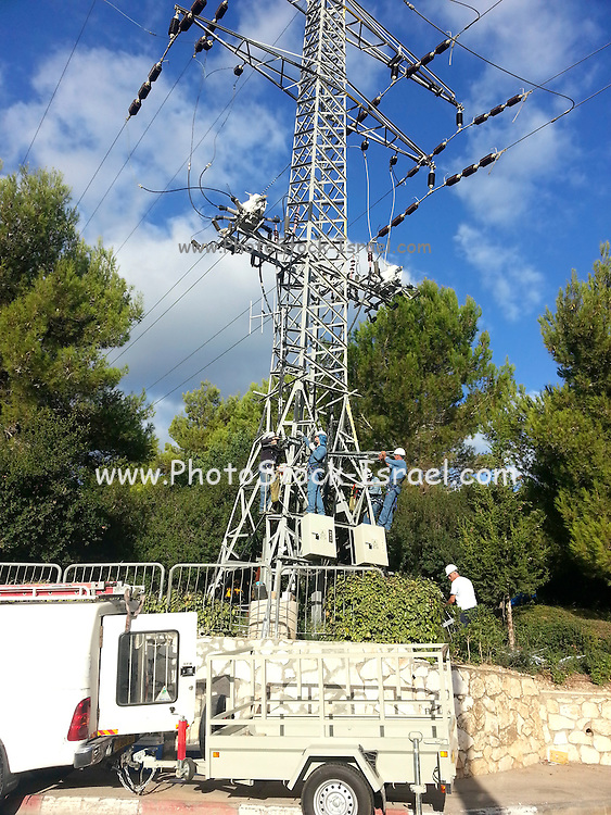 Electricians work on a high voltage pylon Photographed in Israel