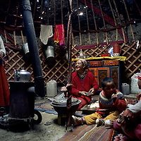 "CHINA. Xinjiang. Nomadic Kyrgyz women prepare tea and lamb fat for dinner inside felt-lined ""akoi"" (yurt) near Lake Karakul."