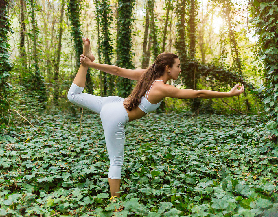 Woman practicing lord of the dance pose outdoors