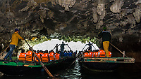 Rowing tourists in a rowboat, Halong Bay, North Vietnam. The bay features 3,000  limestone and dolomite karsts and islets in various shapes and sizes sprinkled over 1,500 square kilometers. It offers a wonderland of karst topography. It is a UNESCO World Heritage Site.