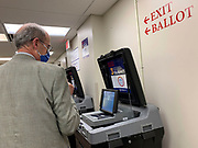 A voter checks that the ballot he put through the optical scanner did indeed go through.