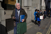 As two women in the background walk in matching blue clothing, an elderly gentleman carries a folder in the same colour, on 10th May 2017, in the City of London, England.