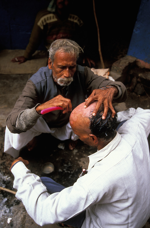 The head of a close male relative of the deceased is shaved before the cremations starts at Manikarnika Ghat, the main cremation site of Varanasi, India
