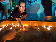 16 NOVEMBER 2013 - BANGKOK, THAILAND: A woman floats a candle to make merit at the Wat Saket temple fair in Bangkok. Wat Saket is on a man-made hill in the historic section of Bangkok. The temple has golden spire that is 260 feet high which was the highest point in Bangkok for more than 100 years. The temple construction began in the 1800s in the reign of King Rama III and was completed in the reign of King Rama IV. The annual temple fair is held on the 12th lunar month, for nine days around the November full moon. During the fair a red cloth (reminiscent of a monk's robe) is placed around the Golden Mount while the temple grounds hosts Thai traditional theatre, food stalls and traditional shows.     PHOTO BY JACK KURTZ
