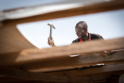 4 June 2019, Meiganga, Cameroon: CAR refugee Mbele Felixe helps dismantle a building in the Ngam refugee camp. Deemed unsafe for use after days of strong wind, the building must be torn down and rebuilt in order to serve again as a distribution for food and other materials to the refugees. Supported by the Lutheran World Federation, the Ngam refugee camp, located in the Meiganga municipality, Adamaoua region of Cameroon, hosts 7,228 refugees from the Central African Republic, across 2,088 households.