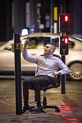© Licensed to London News Pictures . 21/12/2013 . Manchester , UK . A man spins on an office chair in the street as he records himself on his mobile phone . Christmas revellers out in the rain in Manchester on Mad Friday , the last Friday night before Christmas which is typically one of the busiest nights of the year for police and ambulance crews . Photo credit : Joel Goodman/LNP