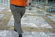 Lower half of an obese man in an orange shirt walking