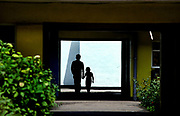 A silhouetted father and daughter holding hands, walk through an archway between buildings, with a white wall behind. There are green bushes and a concrete walk way. they are at a Butlins holiday camp at Skegness. Butlins Skegness is a holiday camp located in Ingoldmells near Skegness in Lincolnshire. Sir William Butlin conceived of its creation based on his experiences at a Canadian summer camp in his youth and by observation of the actions of other holiday accommodation providers, both in seaside resort lodging houses and in earlier smaller holiday campsThe camp began opened in 1936, when it quickly proved to be a success with a need for expansion. The camp included dining and recreation facilities, such as dance halls and sports fields. Over the past 75 years the camp has seen continuous use and development, in the mid-1980s and again in the late 1990s being subject to substantial investment and redevelopment. In the late 1990s the site was re-branded as a holiday resort, and remains open today as one of three remaining Butlins resorts.