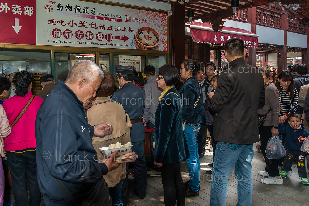 Shanghai, China - April 7, 2013: people eating dim sum Shanghai style steamed pork dumplings in Fang Bang Zhong Lu old city at the city of Shanghai in China on april 7th, 2013