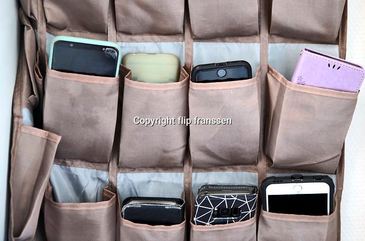 Nederland, Rozendaal, 2-6-2020  Mobieltjes moeten bij de ingaang van de klas, het lokaal, van een middelbare school in een zak met vakjes gedaan worden zodat er tijdens de les niet mee gespeeld of geappt kan worden .Foto: Flip Franssen