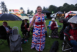 © Licensed to London News Pictures.22/08/15<br /> Castle Howard, North Yorkshire, UK. <br /> <br /> A woman in a Union Flag dress and tiara reacts to the camera as hundreds of people attend the 25th anniversary of the Castle Howard Proms event near York. The theme of the event this year is a commemoration of the 75th anniversary of the Battle of Britain and the 70th anniversary of VE day and brings an evening of classic musical favourites celebrating Britishness to the lawns of Castle Howard.<br /> <br /> Photo credit : Ian Forsyth/LNP
