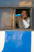 Man in bus window looking bored, Pathein