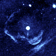 enhanced image from the far-ultraviolet detector on NASA's Galaxy Evolution Explorer shows a ghostly shell of ionized gas around Z Camelopardalis, a binary, or double-star system featuring a collapsed, dead star known as a white dwarf, and a companion star.  Z Cam is the bright object near the centre of the image. Parts of the shell are seen as a lobe-like, light-blue feature below and to the right of Z Cam, and as two large, light blue, perpendicular lines on the left. The massive shell around Z Cam provides evidence of material ejected during and swept up by a powerful nova eruption, called a classical nova, which likely occurred a few thousand years ago.