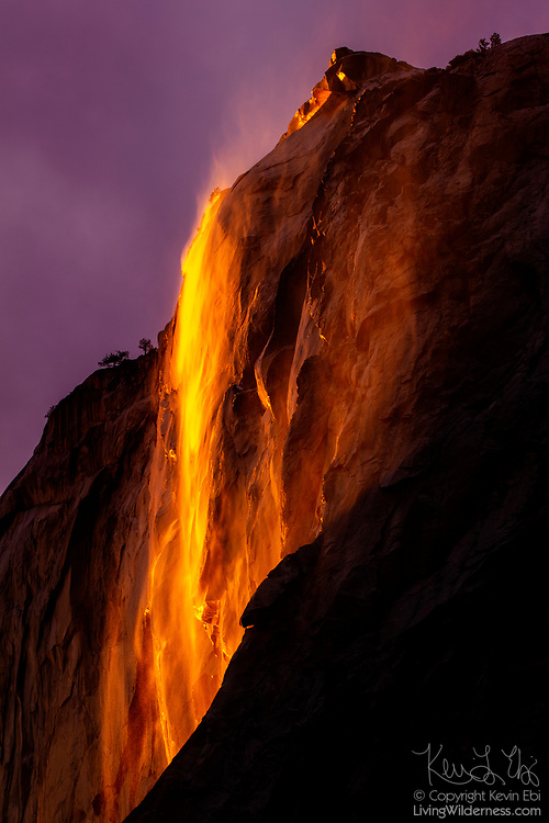 """The water in Horsetail Fall, a 1,000-foot (305-meter) waterfall, appears like lava at sunset as it pours over the granite face of El Capitan in Yosemite National Park, California. The dramatic lighting effect, which has been called a """"firefall,"""" appears in mid-to-late February if the weather conditions are just right."""