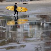 A surfer exits the water at Zuma Beach in Malibu, California.