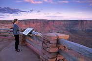 Tourist in evening light takes in the view, Green River Overlook, Island in the Sky, Canyonlands National Park, UTAH
