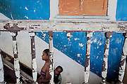 With her child on the back, a young mother is walking the stairs up to their home in Roça Agua Ize', on the island of Sao Tome, Sao Tome and Principe, (STP) a former Portuguese colony in the Gulf of Guinea, West Africa.