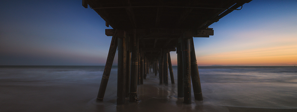 A long exposure elongates the waves that touch the shore beneath the pier at sunset on Port Hueneme Beach. The Channel Island of Anacapa can be seen in the distance.