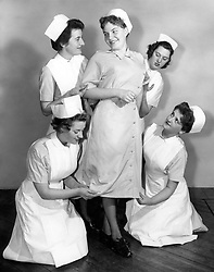 File photo dated 18/12/58 of a new design of uniform being modelled by, then 20-year-old student nurse Gene Williams (centre) at Clatterbridge Hospital, Bebington, Wirral, Cheshire, to be worn by National Health Service (NHS) nurses.