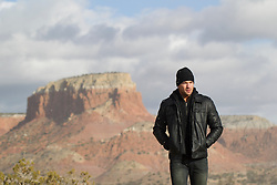 handsome man in a leather jacket walking in Abiquiu, New Mexico