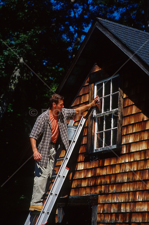 Man on a ladder cleaning the outside of his upstairs window