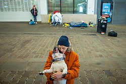 © Licensed to London News Pictures. 25/12/2020. Manchester, UK. Homeless couple NATHAN DALE (25) and AMY DEWHURST (26 (in background) and their dog APACHE , on Market Street in Manchester City Centre on Christmas Day . Photo credit: Joel Goodman/LNP