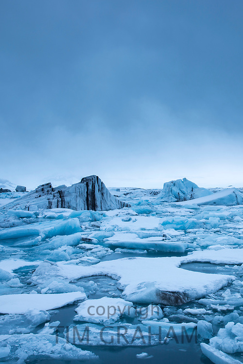 Jokulsarlon glacial lagoon by Vatnajokull National Park. Floating icebergs in blue water from Breioamerkurjokull Glacier, part of Vatnajokull Glacier in South East Iceland to the Atlantic Ocean.