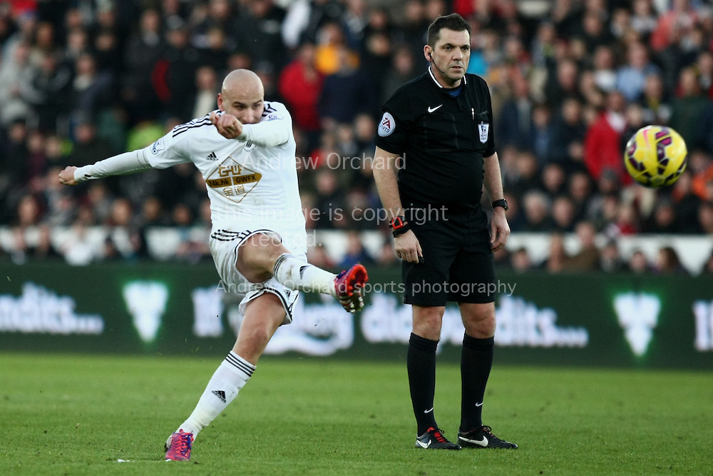 Jonjo Shelvey of Swansea strikes a free kick at goal, under the watch of referee Phil Dowd.<br /> Barclays Premier League match, Swansea City v Sunderland at the Liberty stadium in Swansea, South Wales on Saturday 7th Feb 2015.<br /> pic by Mark Hawkins, Andrew Orchard sports photography.