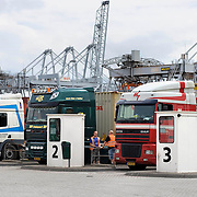 Nederland Zuid-Holland Rotterdam  27-08-2009 20090827 Foto: David Rozing .Serie over logistieke sector.ECT Delta terminal in de haven van Rotterdam. Vrachtwagen chaufeurs maken een praatje terwijl zij wachten op het monent dat de vracht gelost wordt. Telescopische spreader voertuigen vervoeren de containers op de terminal voor verder transport.  .ECT,European Container Terminals, at the Port of Rotterdam. Truck drivers waiting waiting for goods. Europe's biggest and most advanced container terminal operator, handling close to three- quarters of all containers passing through the Port of Rotterdam. ECT is a member of the Hutchison Port Holdings group (HPH), the world biggest container stevedore with terminals on every Continent. At the ECT Delta Terminal telescopic spreader vehicles transport the containers between ship and stack / trucks.  Terminal operations are highly automated for discharging and loading large volumes...Holland, The Netherlands, dutch, Pays Bas, Europe .Foto: David Rozing