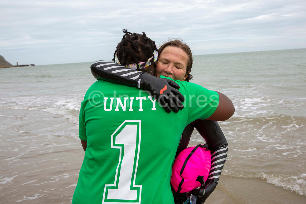 Award winning actress and Folkestone resident Jessica Hynes walks out of the sea to an embrace from Raga Gibreel director of the charity Green Kordofan after completing a 4 mile sea swim with 12 laps of Folkestone sunny sands bay to raise money for charity on the 7th of July 2020 in Folkestone, United Kingdom.  She swam for two different charities, one being the Folkestone community hub, which has been supporting vulnerable people during the Covid-19 lockdown and the second called Green Kordofan which supports children in a refugee camp in Yida, South Sudan. Mrs Hynes is one of many volunteers who have worked at the hub, which provides help by delivering groceries, collecting prescriptions or just being a voice on the end of the phone.The second charity is Green Kordofan, which supports children in a refugee camp in Yida, South Sudan and was founded by Raga Gibreel, also from Folkestone.The registered charity is currently raising money for essential hygiene facilities such as washing and toilet blocks, to make the camp safe for the children who have been displaced by war.
