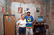 Rafael Teixeira and his mum, Complexo do Alemão 2006.<br /> Now 25 Rafael is living with his wife and 3 year old son in Complexo do Alemao. Rafael has overcome a lot of challenges in his life. In 2006 he had been struggling to stay out of working for the local drug faction he had just raised enough money to replace the roof to the room that he and his mother are standing in. Unfortunately he succumbed to a crack addiction for 2 years until he was helped by AfroReggae and a local church into rehab. He is now working with AfroReggae in Parada de Lucas on a project interviewing and photographing families in the community. He is proud of where he is today and is mainly focused on providing a good life for his wife and children. Part of the series Viver no Meio do Barulho (Living in the Middle of the Noise).